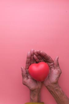 手に赤いハートを持っている年配の女性