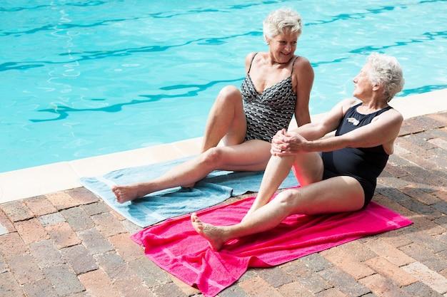 수영장 옆에서 휴식을 취하면서 서로 상호 작용하는 노인 여성