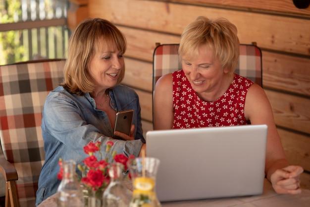 고위 여성들은 집에서 노트북을 사용하여 함께 웃고 있습니다.