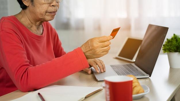 Пожилые женщины ищут кредитную карту и используют ноутбук для покупок в интернете