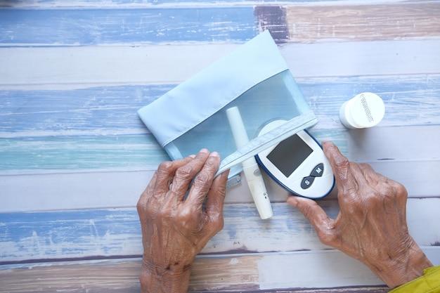 작은 가방에 당뇨병 측정 도구를 넣어 노인 여성