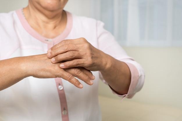 年配の女性は、アトピー性皮膚炎の腕、ヘルスケアおよび医学の概念のかゆみを手で引っかく