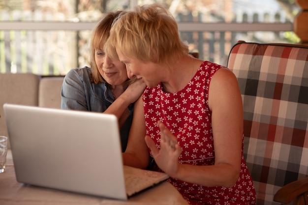 노트북을 사용하여 집에서 함께 시간을 보내는 고위 여성 스톡 사진