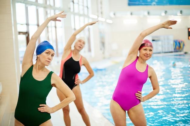年配の女性がプールでトレーニング