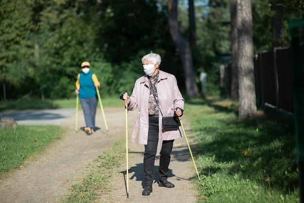 Covid-19 대유행 기간 동안 노르딕 워킹 폴과 함께 걷는 의료 마스크를 착용 한 노인 여성
