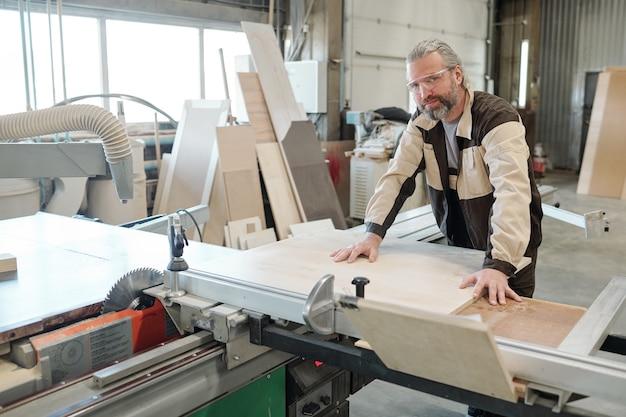 Старший рабочий фабрики по производству мебели фиксирует прямоугольную доску на верстаке перед резкой или шлифовкой с помощью электрического ручного инструмента