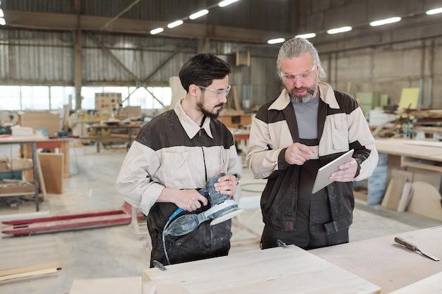 Старший рабочий современной фабрики с помощью тачпада объясняет своему молодому коллеге, как обрабатывать деревянную заготовку с помощью болгарки