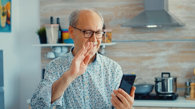 Seniore retired man saying hello during a video call using smarhphone in kitchen while having breakfast. elderly person using internet online chat technology video webcam making a video call connectio