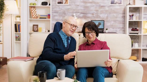 居間のソファに座ってビデオ通話中に高齢者のカップル。現代のテクノロジーを使用する高齢者