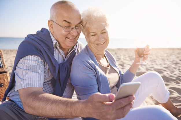 Anziani che bevono vino e guardano il cellulare