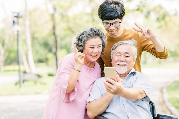 Старшие семьи веселятся со смартфоном