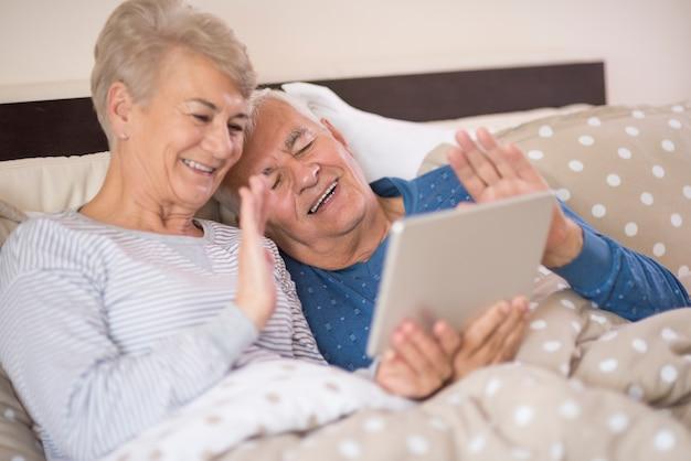 Anziani che hanno una videoconferenza gioiosa