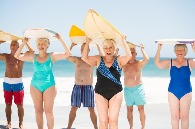 Seniors holding surfboards at the beach