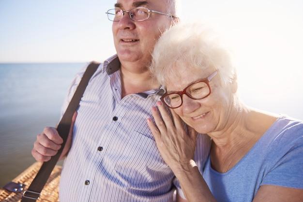 Anziani che si abbracciano mentre vanno a fare un picnic in spiaggia