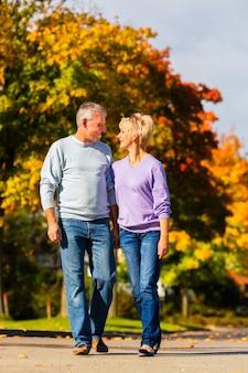 Пожилые люди осенью или осенью ходят рука об руку