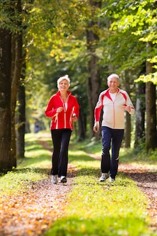 Пожилые люди бегают по лесной дороге