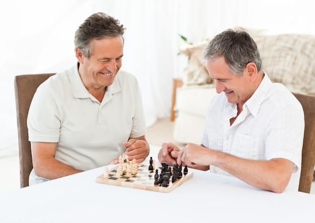 Старшие играют в шахматы на столе