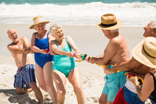 Пожилые люди играют в перетягивание каната на пляже