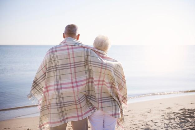Anziani in piedi coperti con una calda coperta in spiaggia