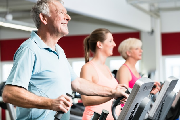 Seniors train on cross trainer with personal trainer at the gym