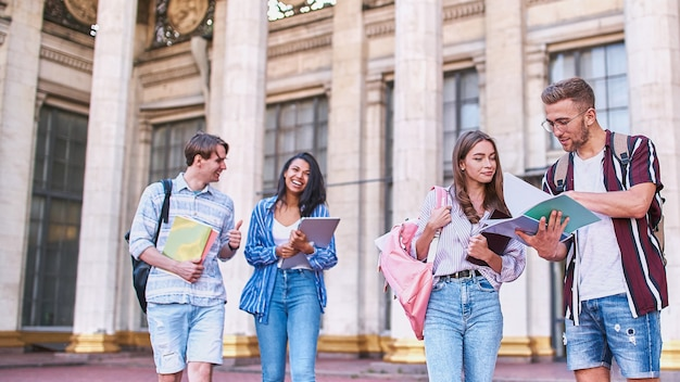 Seniors with folders in hands have fun on the break in the afternoon between classes