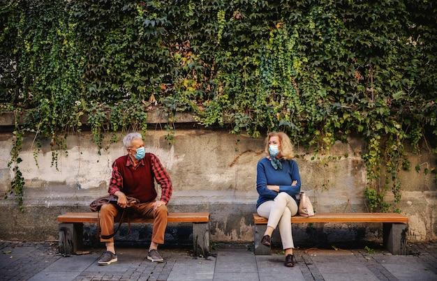 벤치에 앉아 휴식에 보호 마스크와 노인. 노인들은 사회적 거리를 존중합니다.