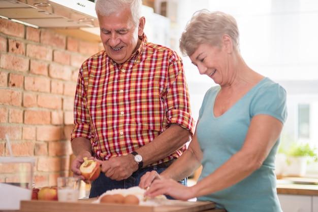 Пожилые люди вместе готовят домашний яблочный пирог