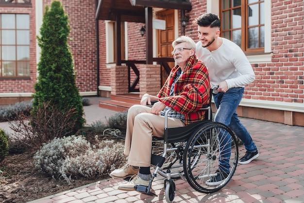 Сениот мужчина встает на инвалидной коляске и его сын помогает ему. рядом с домом престарелых.