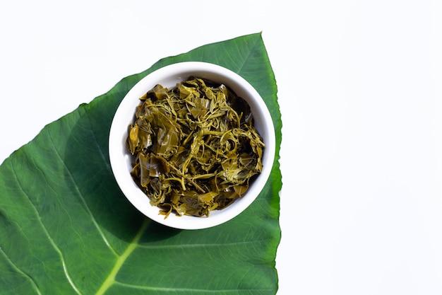 Вареные листья сенны сиамеа в белой миске на листе таро