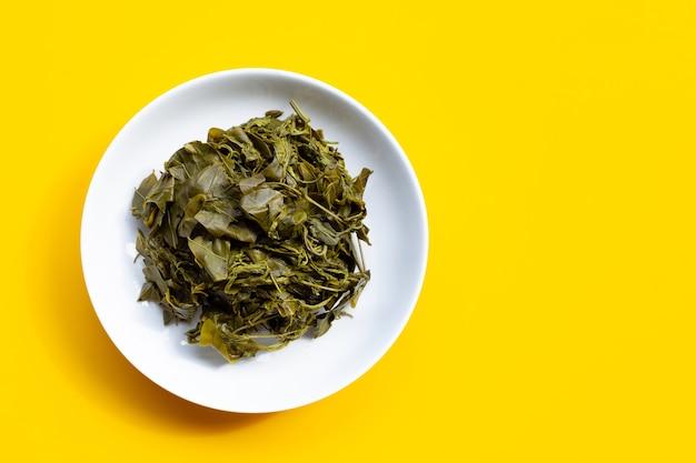 Вареные листья сенны сиамеа в белой тарелке на желтой поверхности