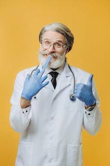 Доктор сеньора, одетый в белое пальто и стетоскоп, изолированный на желтой стене, носит синие перчатки
