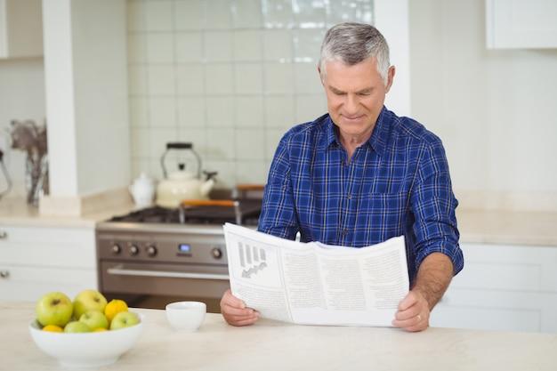 Сеньор мужчина читает газету на кухне