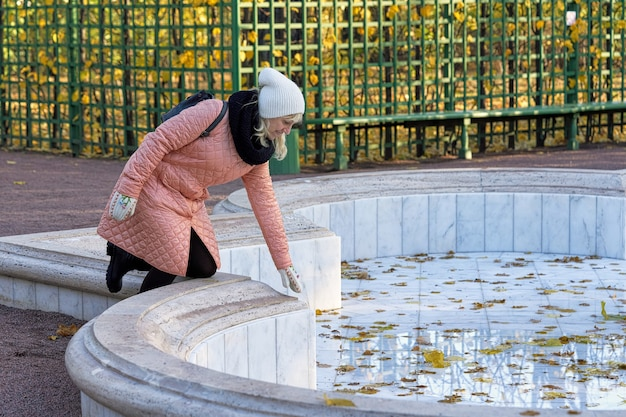 Senora in a pink coat bent into the switched off fountain