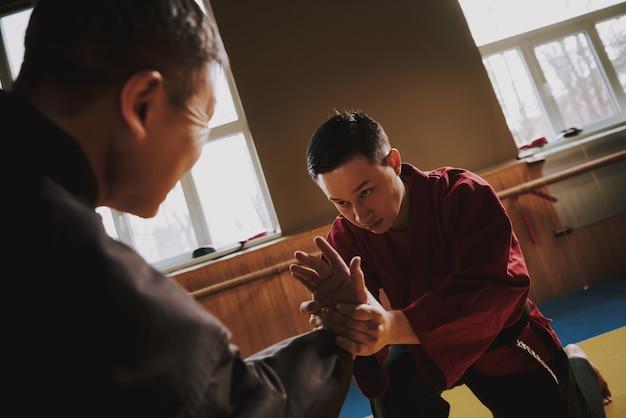 Sensei in black teaching martial arts student.
