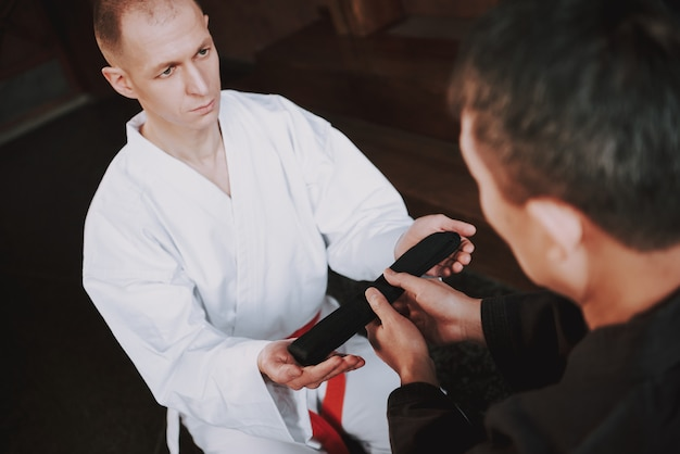 Sensei is giving black belt to martial arts fighter