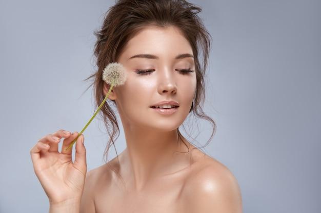 Чувственная красивая девушка с обнаженным макияжем держит одуванчик возле лица и смотрит вниз