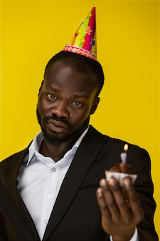Sensitive handsome african man holding a birthday cake.