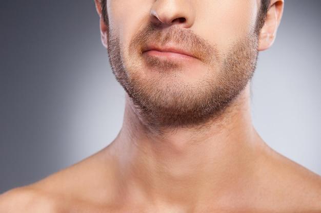 민감한 피부? 회색 배경에 고립되어 서 있는 동안 찡그린 수염을 가진 젊은 남자의 자른 이미지