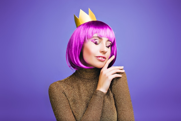 紫の空間で黄金の王冠でカーニバルを祝うおしゃれなうれしそうな若い女性の敏感なスタイリッシュな肖像画。