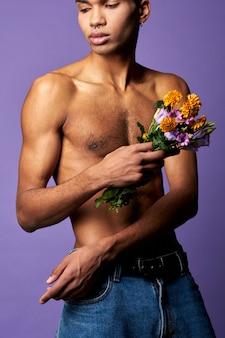 紫色の背景に色とりどりの花を持つ敏感なトランスジェンダーの男性がポートレートショットをクローズアップ