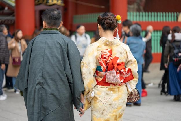 Маленькая девочка нося японское кимоно стоя перед виском sensoji в токио, японии.