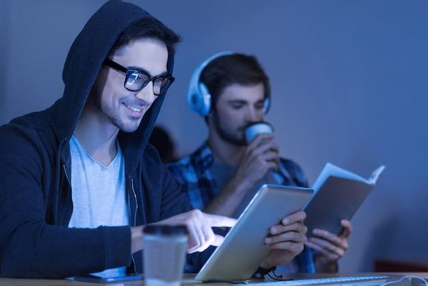 감각 기술. 사무실에 앉아있는 동안 태블릿을 들고 터치 스크린을 누르면 기쁘게 매력적인 긍정적 인 사람