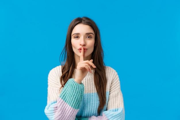 Чувственная и милая, привлекательная молодая брюнетка в зимнем свитере, готовит прекрасный романтический подарок, замалчивает улыбку и прикладывает указательный палец ко рту, молча молча, синий