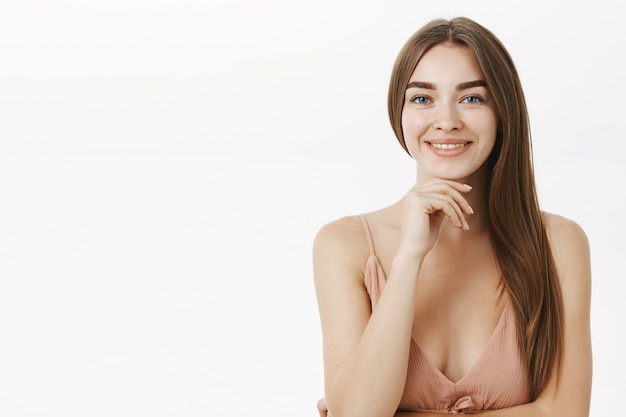 Чувственная и женственная брюнетка в симпатичном бежевом платье, держащая руку за подбородок и широко улыбающаяся с чистой чистой кожей, рада, что у нее нет проблем с минимальным макияжем на серой стене