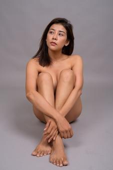 바닥에 앉아있는 동안 벌거 벗은 관능적 인 아시아 여자