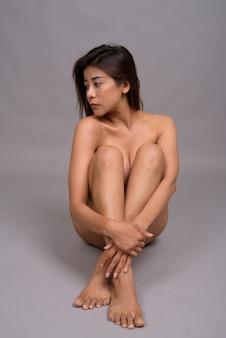 Чувственная азиатская женщина обнаженная, сидя на полу