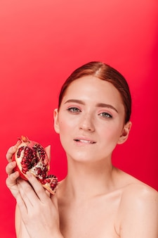 Sensual attractive girl holding garnet. studio shot of refined woman with ripe pomegranate isolated on red background.