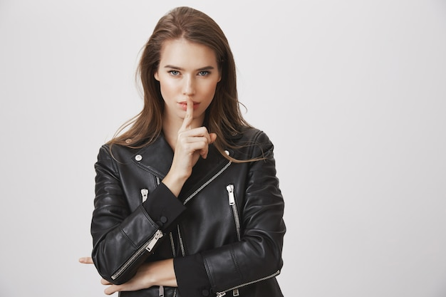 Sensual attractive woman hush with finger pressed to lips