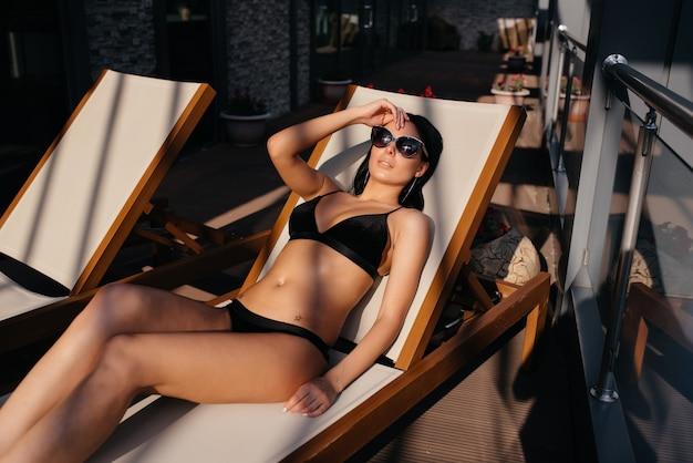 밤에 해변에서 포즈 관능적 인 아름 다운 갈색 머리 여자.