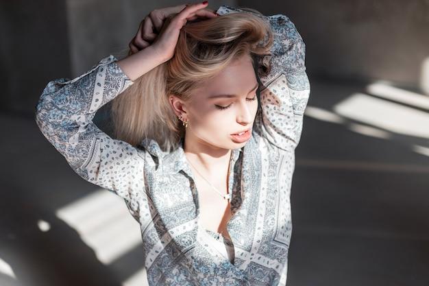 官能的な美しいかわいい若いブロンドの女性、セクシーな唇、自然なメイク、ヴィンテージシャツ、スタジオのパターン